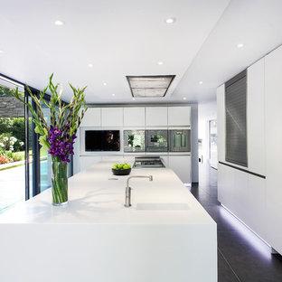 Ejemplo de cocina minimalista con fregadero integrado, armarios con paneles lisos y puertas de armario blancas