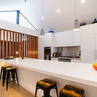 Design ideas for a large contemporary galley eat-in kitchen in Sydney with an integrated sink, white cabinets, metallic splashback, stainless steel appliances, concrete floors, with island, grey floor and white benchtop.