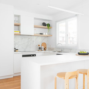 This is an example of a scandinavian u-shaped kitchen in Hobart with a drop-in sink, flat-panel cabinets, white cabinets, grey splashback, stone slab splashback, stainless steel appliances, medium hardwood floors, brown floor and white benchtop.