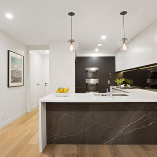 Inspiration for a contemporary u-shaped kitchen in Melbourne with a double-bowl sink, flat-panel cabinets, grey cabinets, black splashback, glass sheet splashback, stainless steel appliances, medium hardwood floors, a peninsula, brown floor and white benchtop.