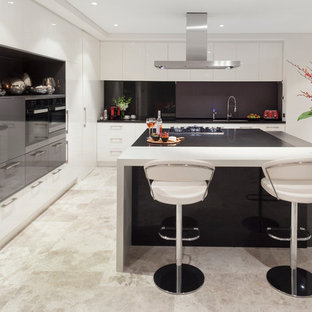 Design ideas for a large contemporary l-shaped eat-in kitchen in Perth with a double-bowl sink, white cabinets, quartz benchtops, black splashback, stone slab splashback, panelled appliances, limestone floors, with island and flat-panel cabinets.