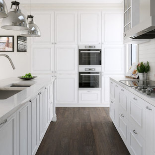 This is an example of a large traditional galley separate kitchen in Melbourne with an undermount sink, raised-panel cabinets, white cabinets, marble benchtops, white splashback, ceramic splashback, stainless steel appliances, with island and dark hardwood floors.