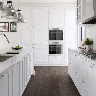 Große, Geschlossene, Zweizeilige Klassische Küche mit Unterbauwaschbecken, profilierten Schrankfronten, weißen Schränken, Marmor-Arbeitsplatte, Küchenrückwand in Weiß, Rückwand aus Keramikfliesen, Küchengeräten aus Edelstahl, Kücheninsel und dunklem Holzboden in Melbourne