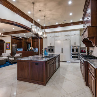 Photo of a large traditional l-shaped kitchen in Dallas with an undermount sink, raised-panel cabinets, dark wood cabinets, granite benchtops, beige splashback, travertine splashback, stainless steel appliances, travertine floors, with island, beige floor and grey benchtop.