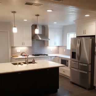 Große Klassische Wohnküche in L-Form mit Einbauwaschbecken, Schrankfronten im Shaker-Stil, hellen Holzschränken, Quarzit-Arbeitsplatte, Rückwand aus Glasfliesen, Küchengeräten aus Edelstahl, Keramikboden, Kücheninsel, Küchenrückwand in Grau, schwarzem Boden und weißer Arbeitsplatte in Los Angeles