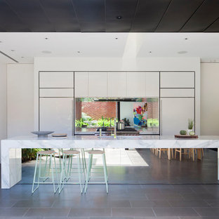 Inspiration for a contemporary galley kitchen in Melbourne with flat-panel cabinets, white cabinets, metallic splashback, mirror splashback, panelled appliances, with island, grey floor and white benchtop.