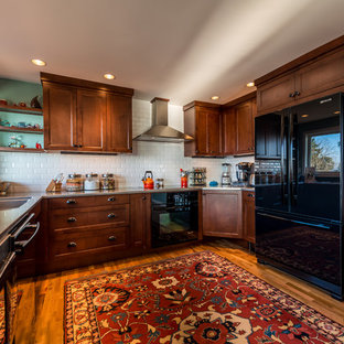 Inspiration for a mid-sized u-shaped open plan kitchen in Seattle with an integrated sink, beaded inset cabinets, dark wood cabinets, granite benchtops, white splashback, ceramic splashback, black appliances, medium hardwood floors and a peninsula.