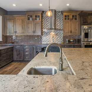 Design ideas for a large country l-shaped open plan kitchen in Philadelphia with a farmhouse sink, raised-panel cabinets, distressed cabinets, quartz benchtops, grey splashback, cement tile splashback, stainless steel appliances, porcelain floors, with island and brown floor.