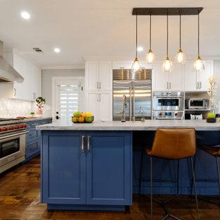 Imagen de cocina en L, clásica renovada, pequeña, abierta, con fregadero sobremueble, armarios estilo shaker, puertas de armario azules, salpicadero blanco, salpicadero de mármol, electrodomésticos de acero inoxidable, suelo de madera en tonos medios, una isla y encimeras azules