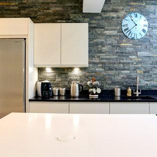 チェシャーの広いコンテンポラリースタイルのおしゃれなキッチン (ドロップインシンク、フラットパネル扉のキャビネット、珪岩カウンター、ライムストーンのキッチンパネル、シルバーの調理設備、クッションフロア) の写真