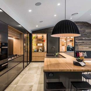 Diseño de cocina comedor en L, contemporánea, con fregadero bajoencimera, puertas de armario negras, encimera de madera, salpicadero negro, electrodomésticos negros, suelo de baldosas de porcelana, una isla, suelo gris y armarios con paneles lisos