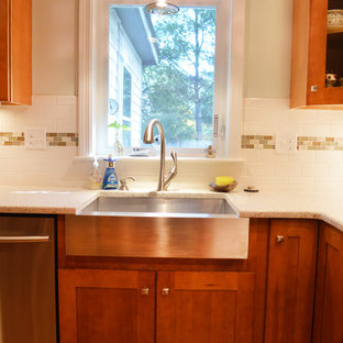 This is an example of a mid-sized transitional u-shaped eat-in kitchen in Boston with a farmhouse sink, shaker cabinets, medium wood cabinets, recycled glass benchtops, white splashback, subway tile splashback, stainless steel appliances, medium hardwood floors, no island and white benchtop.