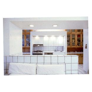Ispirazione per un'ampia cucina con lavello da incasso, ante lisce, ante in legno scuro, top piastrellato, paraspruzzi bianco, paraspruzzi con piastrelle in ceramica, elettrodomestici da incasso, pavimento con piastrelle in ceramica e isola