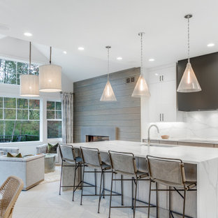 Large contemporary open concept kitchen ideas - Large trendy galley white floor open concept kitchen photo in Grand Rapids with an undermount sink, flat-panel cabinets, light wood cabinets, white backsplash, paneled appliances, an island and white countertops