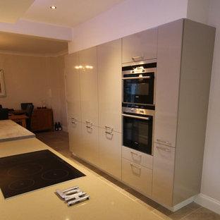 他の地域の中サイズのコンテンポラリースタイルのおしゃれなキッチン (ダブルシンク、フラットパネル扉のキャビネット、グレーのキャビネット、ラミネートカウンター、白いキッチンパネル、レンガのキッチンパネル、カラー調理設備、大理石の床、グレーの床) の写真