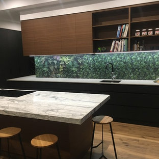 Photo of a large traditional galley open plan kitchen in Adelaide with a drop-in sink, black cabinets, marble benchtops, green splashback, porcelain splashback, porcelain floors, with island, louvered cabinets, black appliances, brown floor and white benchtop.