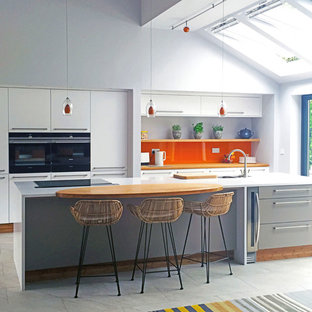 This is an example of a large modern open plan kitchen in Other with an integrated sink, flat-panel cabinets, orange splashback, glass sheet splashback, black appliances and with island.