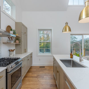 Design ideas for a mid-sized transitional single-wall eat-in kitchen in Other with an undermount sink, shaker cabinets, beige cabinets, quartz benchtops, white splashback, ceramic splashback, stainless steel appliances, bamboo floors, with island, brown floor and white benchtop.