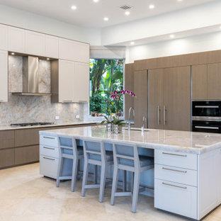マイアミの巨大なコンテンポラリースタイルのおしゃれなキッチン (アンダーカウンターシンク、フラットパネル扉のキャビネット、淡色木目調キャビネット、珪岩カウンター、ベージュキッチンパネル、パネルと同色の調理設備、トラバーチンの床、ベージュの床、ベージュのキッチンカウンター) の写真