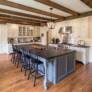 Geräumige Klassische Küche in L-Form mit Landhausspüle, Kassettenfronten, beigen Schränken, Speckstein-Arbeitsplatte, Küchenrückwand in Beige, Küchengeräten aus Edelstahl, braunem Holzboden, Kücheninsel, braunem Boden und schwarzer Arbeitsplatte in Philadelphia