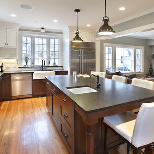 Large contemporary eat-in kitchen photos - Large trendy l-shaped light wood floor eat-in kitchen photo in Minneapolis with shaker cabinets, stainless steel appliances, an island, granite countertops, gray backsplash and a farmhouse sink