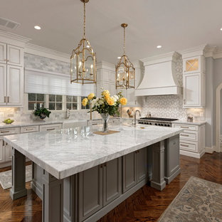 Large traditional eat-in kitchen inspiration - Large elegant l-shaped dark wood floor and brown floor eat-in kitchen photo in DC Metro with a farmhouse sink, recessed-panel cabinets, white cabinets, multicolored backsplash, stainless steel appliances, an island, multicolored countertops, marble countertops and mosaic tile backsplash