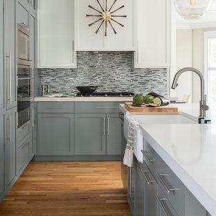 Klassische Küche mit Landhausspüle, Schrankfronten im Shaker-Stil, grauen Schränken, bunter Rückwand, Rückwand aus Stäbchenfliesen, Küchengeräten aus Edelstahl, Kücheninsel, weißer Arbeitsplatte und hellem Holzboden in Denver