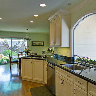 This is an example of a mid-sized traditional galley eat-in kitchen in San Francisco with a drop-in sink, black splashback, stainless steel appliances, white cabinets, recessed-panel cabinets, granite benchtops, light hardwood floors and a peninsula.