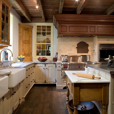 Inspiration for a large timeless l-shaped dark wood floor and brown floor enclosed kitchen remodel in Philadelphia with a farmhouse sink, travertine backsplash, recessed-panel cabinets, white cabinets, marble countertops, beige backsplash, stainless steel appliances and an island