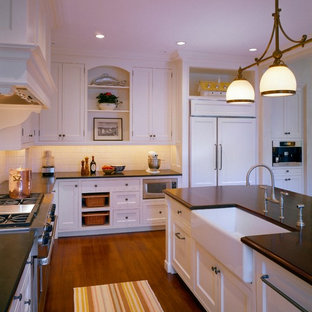 Large farmhouse open concept kitchen pictures - Inspiration for a large cottage u-shaped medium tone wood floor and brown floor open concept kitchen remodel in Boston with recessed-panel cabinets, white cabinets, granite countertops, an island, a farmhouse sink, red backsplash, ceramic backsplash and stainless steel appliances