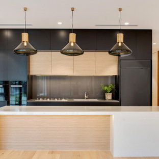 Design ideas for a large contemporary galley kitchen in Adelaide with an integrated sink, flat-panel cabinets, black cabinets, grey splashback, glass sheet splashback, panelled appliances, with island, beige floor and beige benchtop.