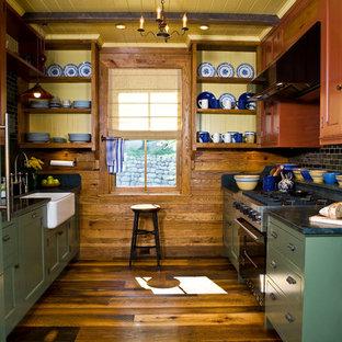 Inredning av ett rustikt parallellkök, med en rustik diskho, skåp i shakerstil, svart stänkskydd, stänkskydd i tunnelbanekakel, svarta vitvaror och mellanmörkt trägolv