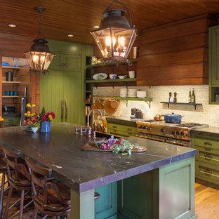 グランドラピッズの巨大なラスティックスタイルのおしゃれなアイランドキッチン (エプロンフロントシンク、シェーカースタイル扉のキャビネット、緑のキャビネット、ベージュキッチンパネル、シルバーの調理設備の、無垢フローリング、黒いキッチンカウンター) の写真