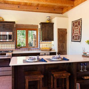 フェニックスの小さいサンタフェスタイルのおしゃれなキッチン (アンダーカウンターシンク、シェーカースタイル扉のキャビネット、濃色木目調キャビネット、クオーツストーンカウンター、マルチカラーのキッチンパネル、セメントタイルのキッチンパネル、シルバーの調理設備、レンガの床、ベージュのキッチンカウンター、板張り天井) の写真