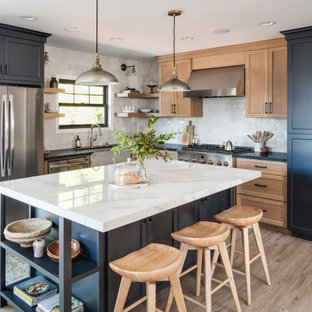 This is an example of a medium sized traditional l-shaped kitchen/diner in San Diego with a belfast sink, shaker cabinets, blue cabinets, composite countertops, white splashback, terracotta splashback, black appliances, vinyl flooring, an island, beige floors and black worktops.