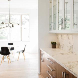 Foto di una cucina moderna di medie dimensioni con lavello sottopiano, ante lisce, ante bianche, top in marmo, paraspruzzi bianco, paraspruzzi in lastra di pietra, elettrodomestici da incasso, pavimento in legno massello medio e isola