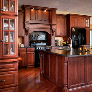 Inspiration for an expansive traditional l-shaped eat-in kitchen in Omaha with an undermount sink, raised-panel cabinets, dark wood cabinets, granite benchtops, black splashback, ceramic splashback, black appliances, dark hardwood floors and with island.