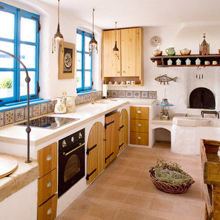 Photo of a small mediterranean u-shaped eat-in kitchen in Other with an integrated sink, open cabinets, medium wood cabinets, limestone benchtops, multi-coloured splashback, ceramic splashback, white appliances, brick floors and no island.