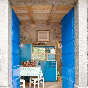 Medelhavsstil inredning av ett litet kök, med en enkel diskho, öppna hyllor, blå skåp, träbänkskiva, beige stänkskydd, stänkskydd i sten, vita vitvaror och tegelgolv