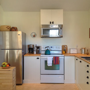Small bohemian l-shaped kitchen in Denver with a double-bowl sink, beaded cabinets, white cabinets, wood worktops, white splashback, ceramic splashback, stainless steel appliances, plywood flooring and an island.