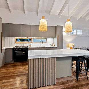 Inspiration for a small contemporary l-shaped eat-in kitchen in Brisbane with an undermount sink, grey cabinets, quartz benchtops, grey splashback, window splashback, black appliances, with island, white benchtop, flat-panel cabinets, medium hardwood floors, brown floor and exposed beam.