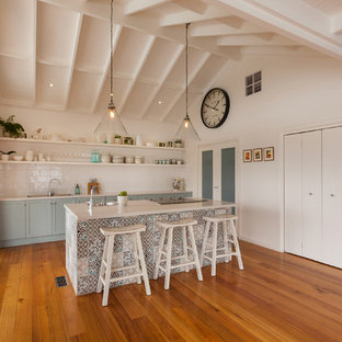 Beach style galley open plan kitchen in Other with a drop-in sink, shaker cabinets, blue cabinets, white splashback, subway tile splashback, panelled appliances, medium hardwood floors, with island, brown floor and white benchtop.