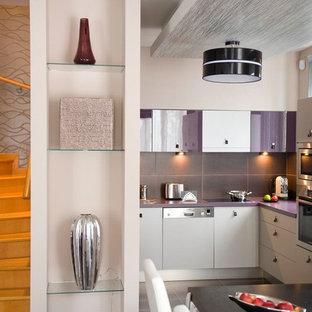 Moderne Wohnküche mit flächenbündigen Schrankfronten, Elektrogeräten mit Frontblende, Küchenrückwand in Grau, Rückwand aus Steinfliesen, weißen Schränken und lila Arbeitsplatte in Sonstige