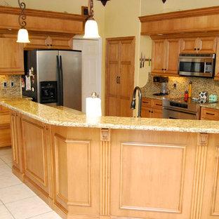 Bild på ett mellanstort vintage kök, med en undermonterad diskho, luckor med upphöjd panel, skåp i ljust trä, granitbänkskiva, beige stänkskydd, stänkskydd i sten, rostfria vitvaror, klinkergolv i keramik, en köksö och beiget golv