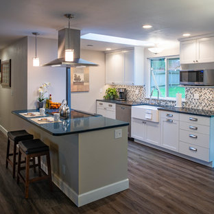 This is an example of a mid-sized contemporary galley kitchen in Seattle with shaker cabinets, white cabinets, quartz benchtops, grey splashback, laminate floors, grey floor and blue benchtop.