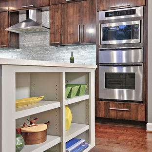 Mid-sized trendy single-wall medium tone wood floor open concept kitchen photo in Austin with an undermount sink, flat-panel cabinets, dark wood cabinets, quartz countertops, gray backsplash and stainless steel appliances