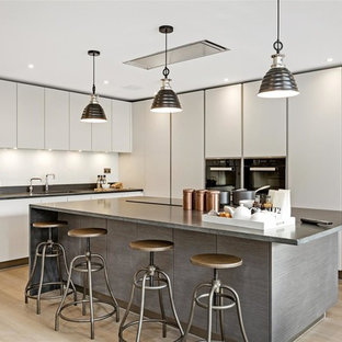 Medium sized contemporary l-shaped kitchen in London with a submerged sink, flat-panel cabinets, white splashback, stainless steel appliances, an island, beige floors and black worktops.