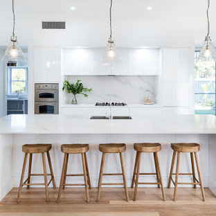 This is an example of a beach style open plan kitchen in Sunshine Coast with an undermount sink, shaker cabinets, white cabinets, white splashback, stainless steel appliances, light hardwood floors, with island and beige floor.