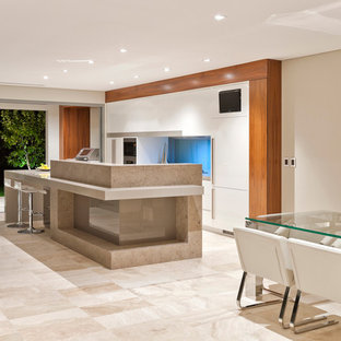 This is an example of a mid-sized contemporary galley eat-in kitchen in Perth with louvered cabinets, white cabinets, quartz benchtops, blue splashback, glass sheet splashback, stainless steel appliances, travertine floors and with island.