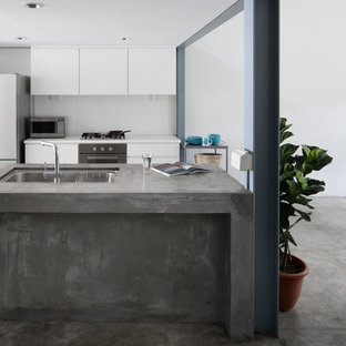Inspiration for an industrial galley kitchen in Singapore with a drop-in sink, flat-panel cabinets, white cabinets, concrete benchtops, white splashback, white appliances, concrete floors, multiple islands, grey floor and grey benchtop.